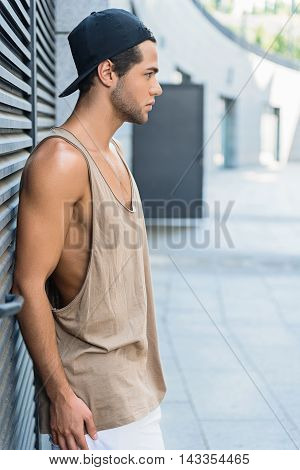 Stylish hipster boy is standing and leaning on wall outdoors. He is looking forward seriously. Guy is wearing cap