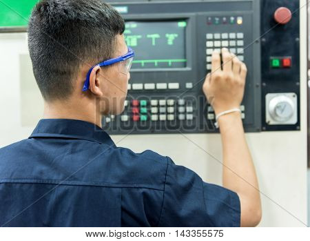 CNC operator mechanical technician worker at metal machining milling center in tool workshop inserting data with keyboard wearing