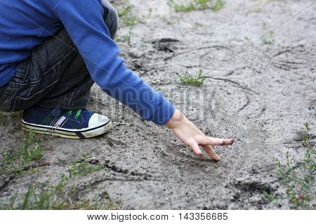 Developmental activities in the fresh air. The child sits down and draws a finger in the sand of different shapes.