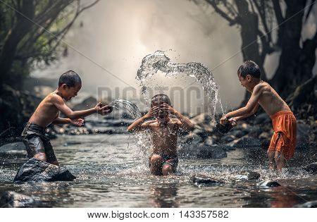 Three boy joyful with splashing, Thailand countryside