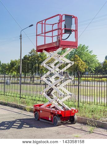 Mobile aerial work platform - red and white scissor hydraulic self propelled lift