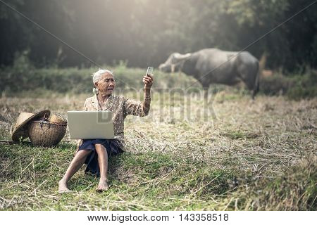 Old woman using a laptop and telephone outdoor