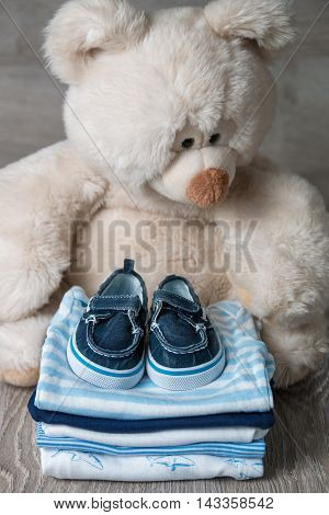 Folded Blue And White Bodysuit With Shoes On It Near Big Teddy Bear  Grey Wooden Background. Diaper