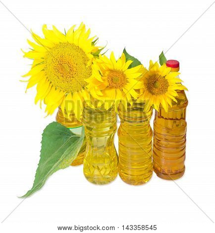 Several plastic bottles of sunflower oil of different variety and sunflower flowers and leaves on a light background