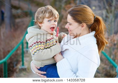 Mother and little son in park or forest, outdoors. Hugging and having fun together.