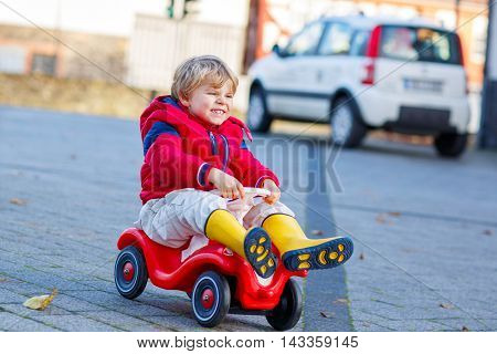 Funny cute kid boy in colorful fashion clothes driving toy car. child having fun, outdoors. Active children leisure in autumn