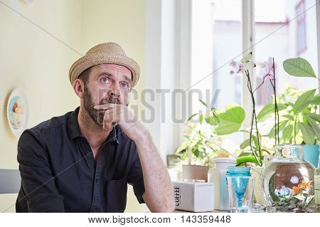 Man With Hat And Beard Sitting And Pondering