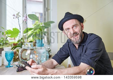 Man With Hat And Beard Happy Looking At Phone And Soap Bubbles In The Air