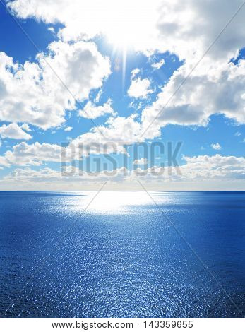 Sea scene with sparkling water and fluffy cloudscape. Copy space and open water.