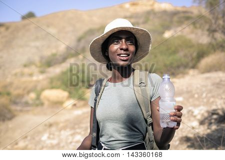Woman holding a bottle of water in a hot summer day