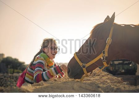 Happy blonde girl caressing a horse