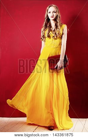 Fashion Woman in an Elegant Silk Dress. Curly Blonde Hair Yellow Dress and Red Background