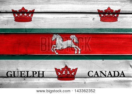 Flag Of Guelph, Canada, Painted On Old Wood Plank Background