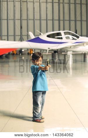 7 years old Asian boy dream to fly play flying toy in hangar with airplane background in vintage color