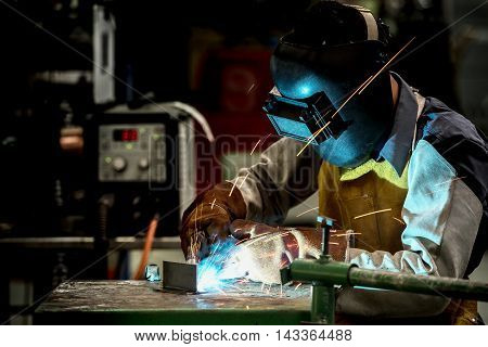 Industrial welding worker at the factory welding steel with safety protective mask