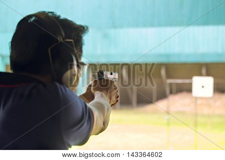 law enforcement aim pistol by two hand in academy shooting range focus on pistol in vintage color
