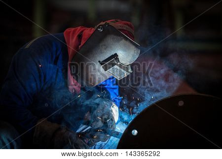 Industrial welding worker at the factory welding steel joint with safety protective mask