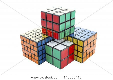 Coventry West Midlands UK - Aug 19 2016: Rubik's style retro puzzle cubes from the 80's solved and stacked in a pile on an isolated white background with a clipping path