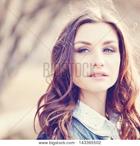 Portrait of Young Beautiful Woman on Sunny Nature Background