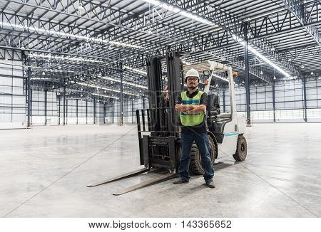Engineer working and standing in empty warehouse