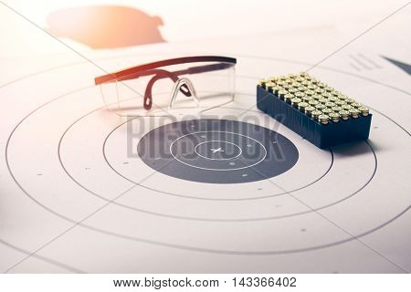 x on paper target with safety glasses and 9 mm bullet with flare and vintage color focus on 'x'