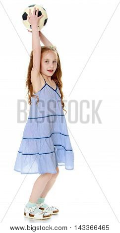 Joyful little girl with long pigtails to her waist and braided white bows. In a long blue dress. Standing sideways to the camera and holding up a soccer ball - Isolated on white background