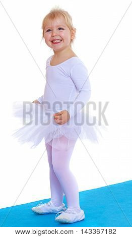 Cheerful little girl is a future gymnast, white sports dress, standing on a blue sports Mat-Isolated on white background