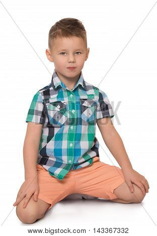 Beautiful little boy in shirt with short sleeves and shorts. The boy sits on the floor. - Isolated on white background