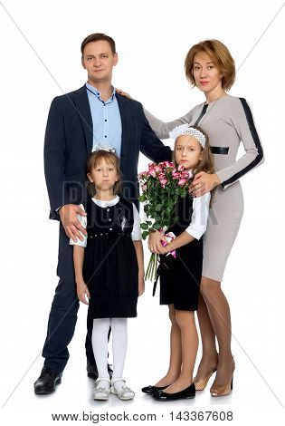 Family portrait of 4 people. Parents with two adorable school-age girls , with a bouquet of roses - Isolated on white background
