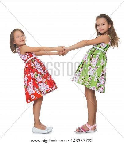 Two beautiful little girls in fancy dresses holding hands- Isolated on white background