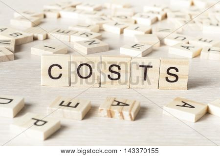 COSTS word concept on wood cubes. Wooden ABC.