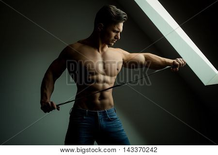 Sexy young man with muscular body and bare torso posing near window holding leather belt