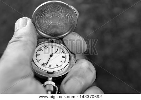 A pocket watch with an open shield in a male hand closeup in black and white