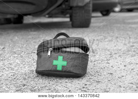 First aid kit in the foreground and cars in the blurred background selective color outdoor shot