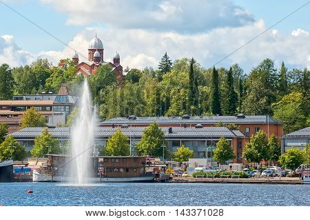 LAPPEENRANTA, FINLAND - AUGUST 8, 2016:  Summer landscape with fountain and boats in Lappeenranta Harbor on Saimaa Lake. On the background is City Lutheran Church