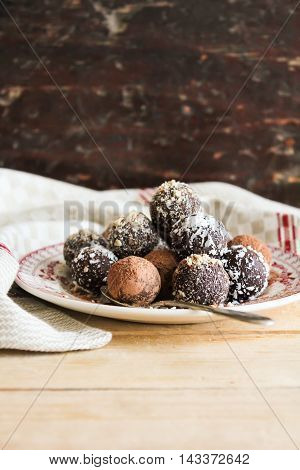 Homemade dark chocolate truffles with cocoa powder, freshly shredded coconut and chopped hazelnuts on a dessert plate, selective focus