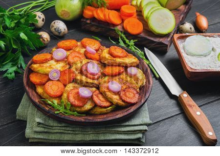 Vegetables ingredients for fried vegetable dishes in dough. Vegetables marrows white squashes carrots parsley lettuce dill tomato onions quail eggs flour. Black wood background.