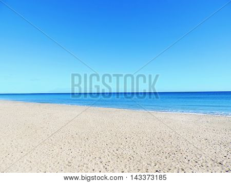 Empty beach scene with white sand, turquoise sea and clear blue sky with copy space. Beach background.