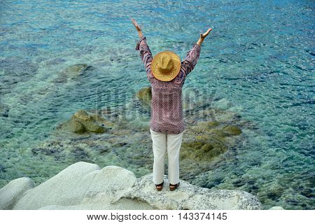 Woman with hands up standing on the rock near the sea. Selective focus.