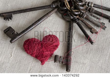 red heart with metal keys on background in beige canvas
