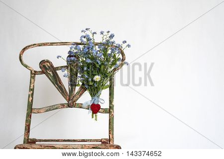 bouquet of blue flowers with heart tied up to the backrest of an old chair in iron, white background