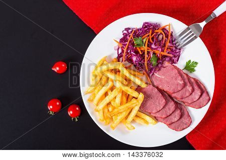 french fries and sliced smoked meat with cabbage salad on white plate on cutting board with mustard in gravy boat and spices on porcelain spoons view from above