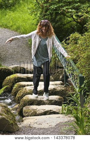 A Woman Holds a Railing as She Tentatively Crosses a Creek on Stepping Stones