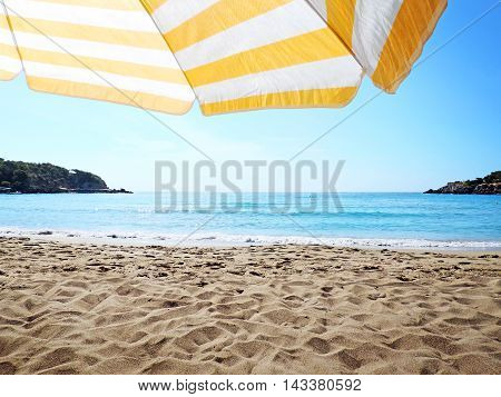 Beach background with yellow and white striped sunshade and view to the sea.