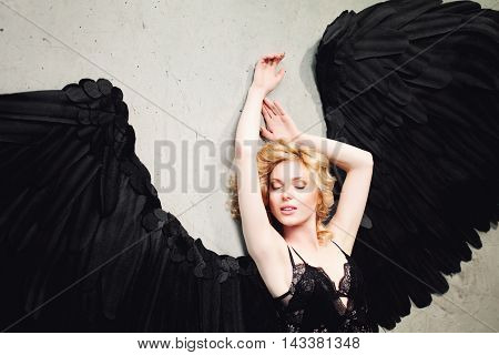 Sexy Woman with Angel Wings Relaxing on the Floor