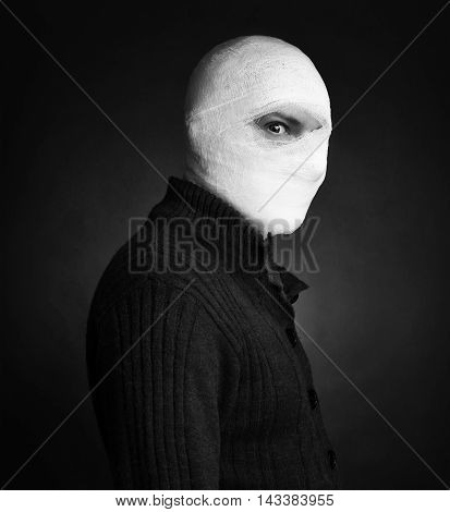 Head tied up by bandage in a grey background