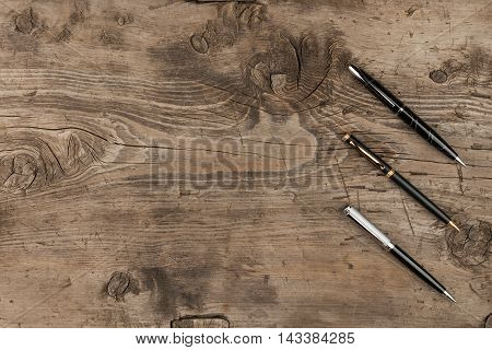 Black gold and silver pens on a wooden texture with place for your text