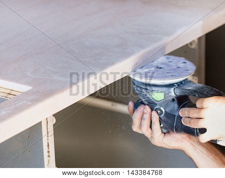 Worker Sanding Worktop From Artificial Stone
