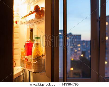 Open Door Of Refrigerator With Food In Evening
