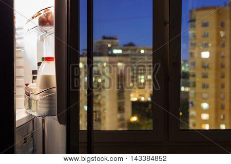 Open Refrigerator With Milk Bottles In Night